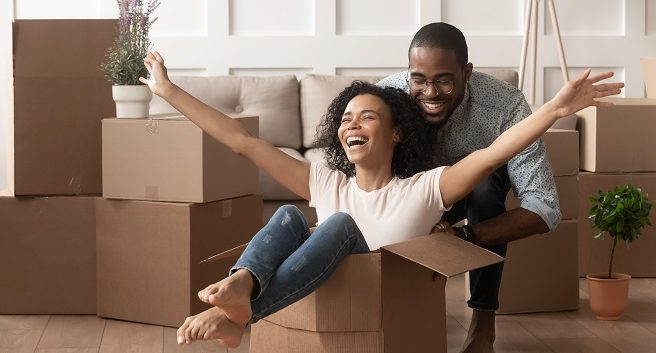 excited couple in new home, woman in box with arms out and man behind her celebrating