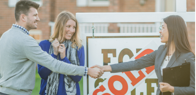 happy couple buying a new home shaking hands with real estate agent in from of sold sign.
