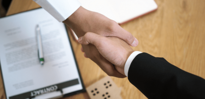 handshake over home cutout and paperwork to depict homebuyer tips for first home