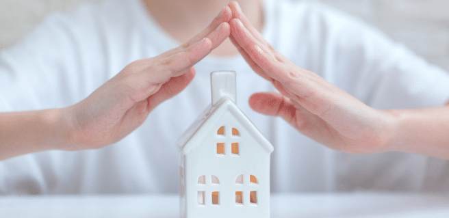 Photo of two hands covering a home to depict home warranties and their importance.