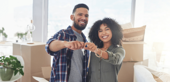 Happy couples hold keys to house to depict millennials