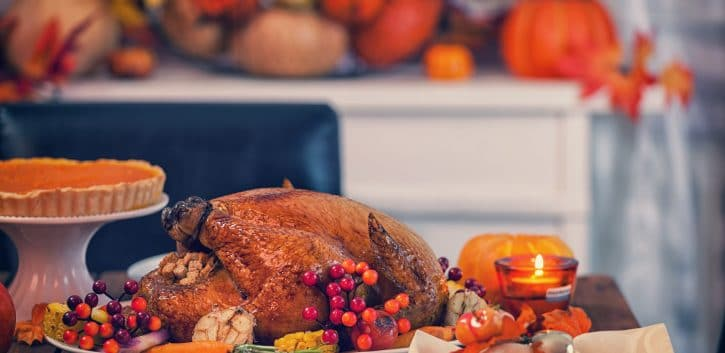 Table is set up for celebrating Thanksgiving. On the table is a traditional roasted turkey with side dishes and autumn decoration. Atlanta restaurants open on Thanksgiving