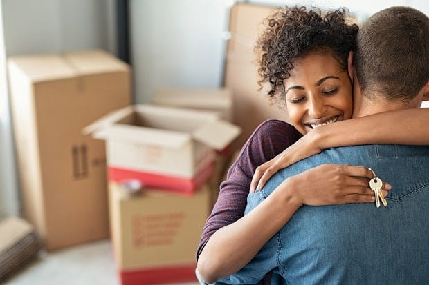 Couple hugging holding house keys with boxes in background at new home