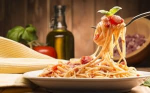 spaghetti twirled on a forkk over a plate of sphagetti