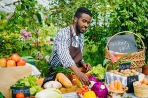 man arranges produce at a farmers market
