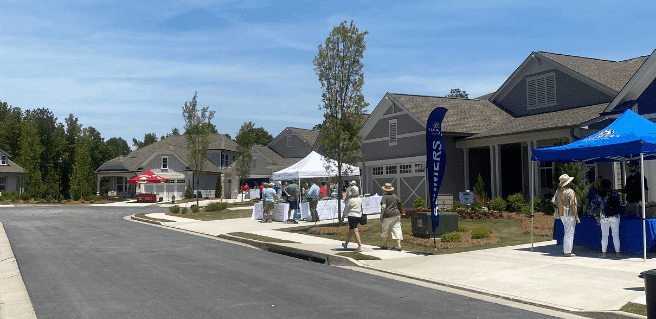 streetscape view of people mingling for oschton Day at Cresswind Georgia at Twin Lakes