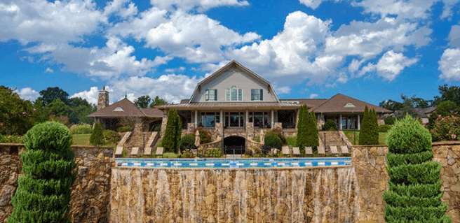 view of Sterling on the Lake community clubhouse exterior with view of pool edge and waterfall