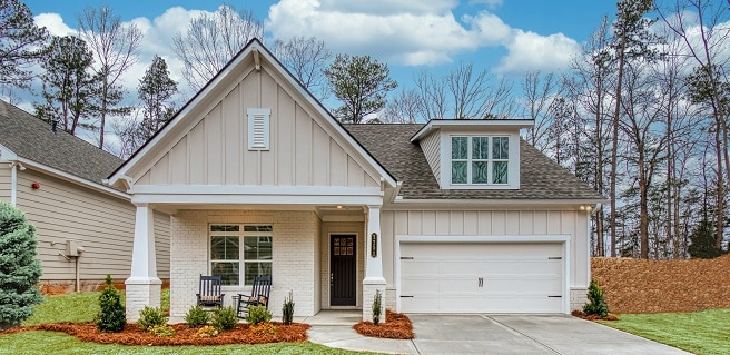 front of home at Courtyards at Hickory Flats in Cherokee by Traton Homes. White house with columns, grass and landscaping.