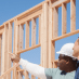 3 people on a job site where a home is being framed to depict housing boom