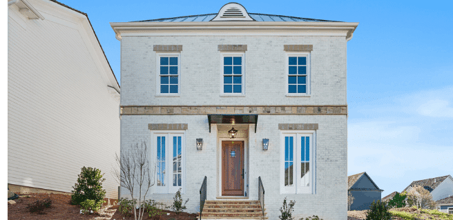 Two story white brick home built by Southwyck Homes at Vickery features a metal roof, brick and stone, large windows and stained wood front door and interesting lighting features.