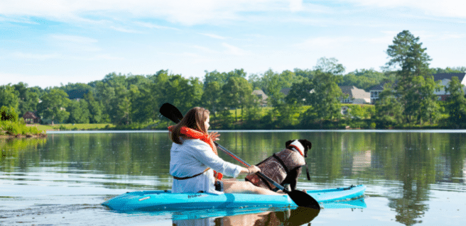 Photo of a woman canoeing with a dog to advertise lakeside living in Sterling on the Lake