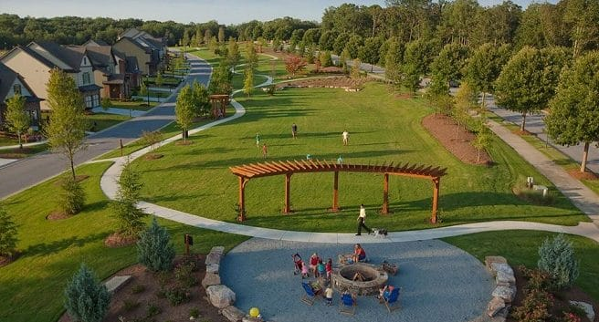 Overview of Sterling on the Lake trails connecting green grassy area with fire pit and family gathered around